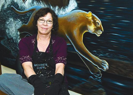 "Judith Lowry sits in front of her painting ""The Race for Fire"" which will be on display at the Roseville Maidu Interpretive Center in Roseville, Calif."